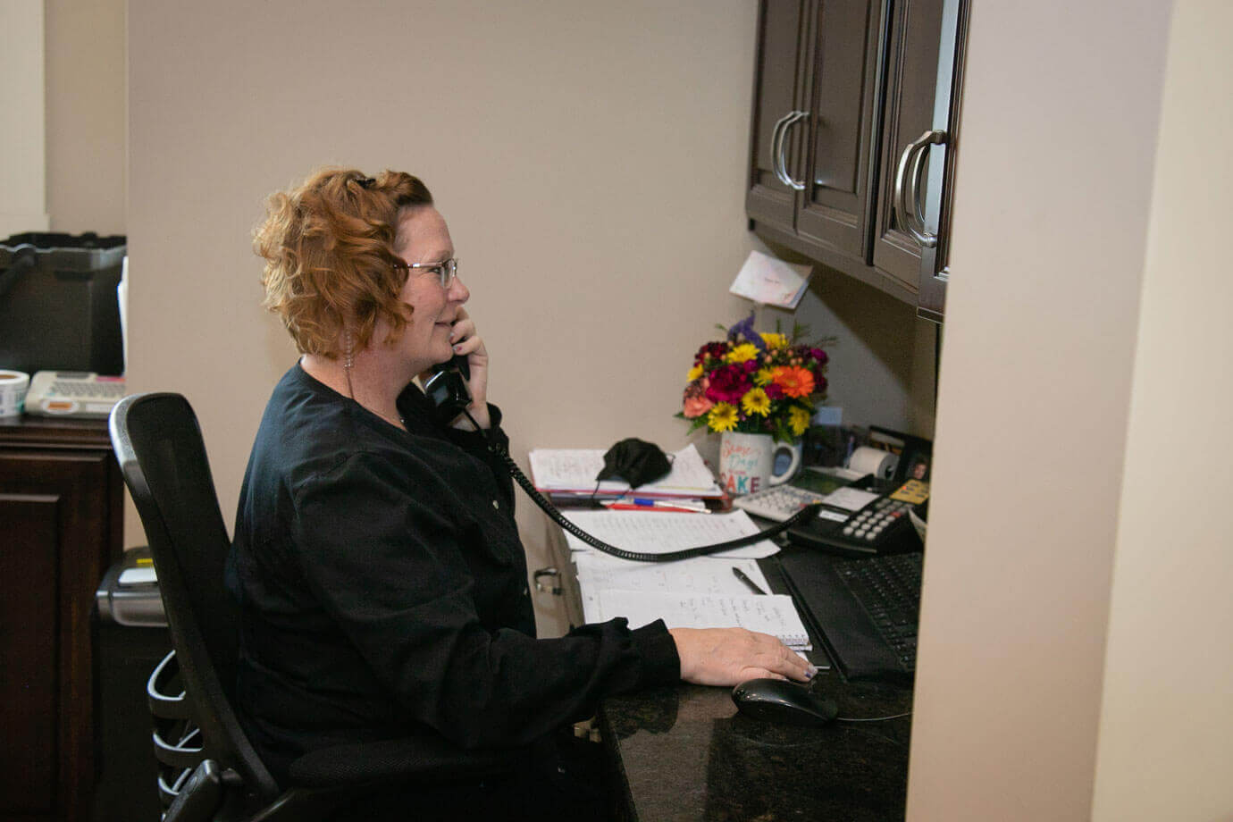 staff member at green dental on the phone with patient